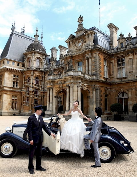 Jaguar Drophead with the Bride, Groom and chauffeur opening the door. Waddesdon manor features in the background