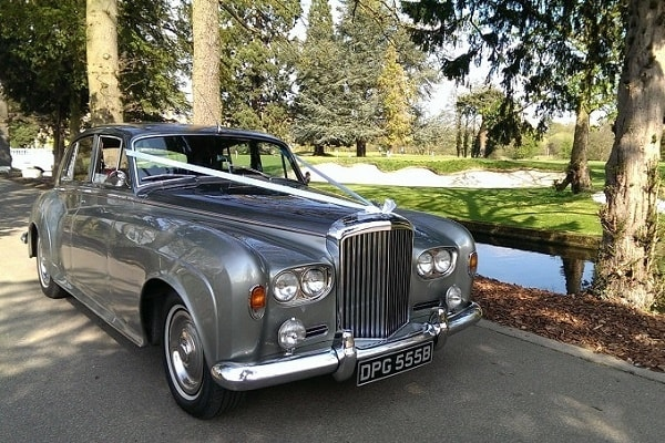 Our Silver Bentley S3 wedding car decorated with ribbons and bows